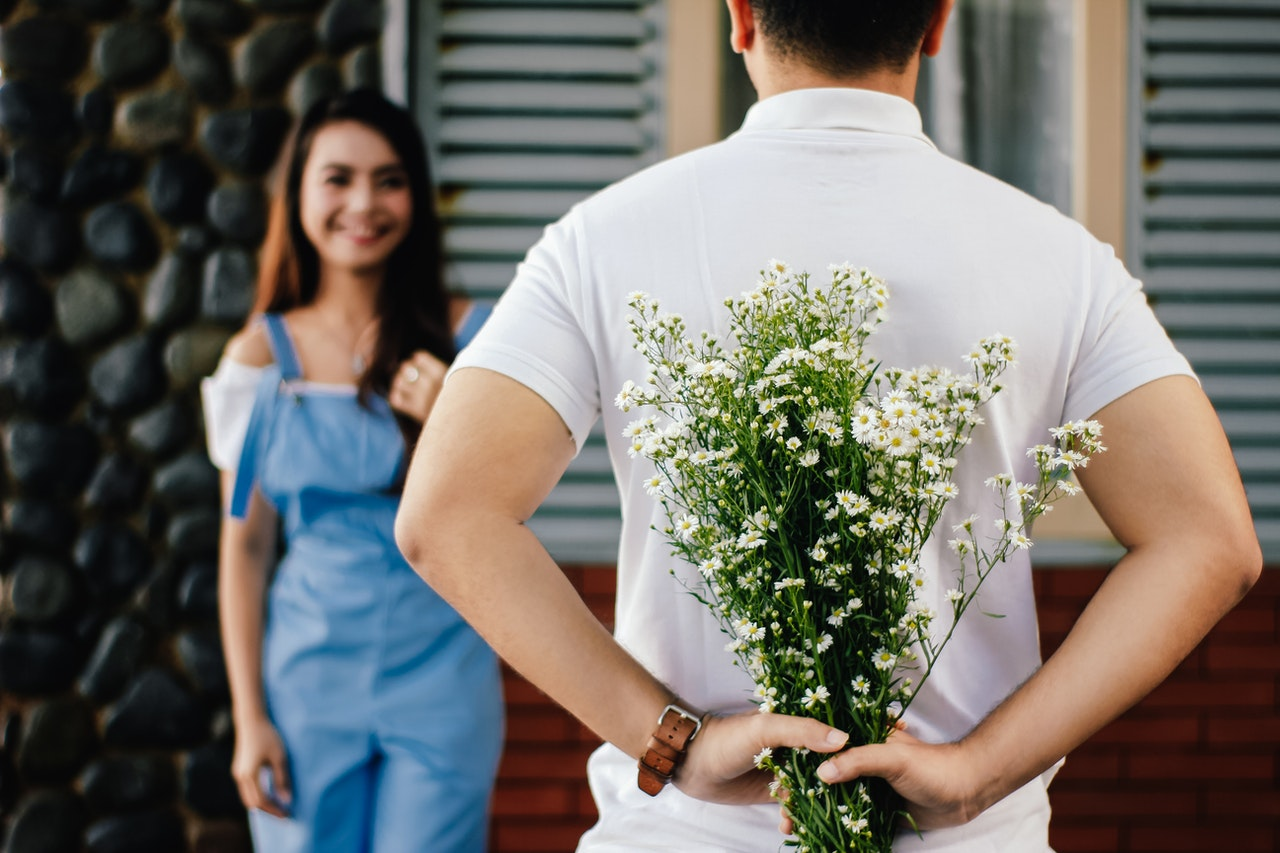 man-holding-baby-s-breath-flower-in-front-of-woman-standing-935789