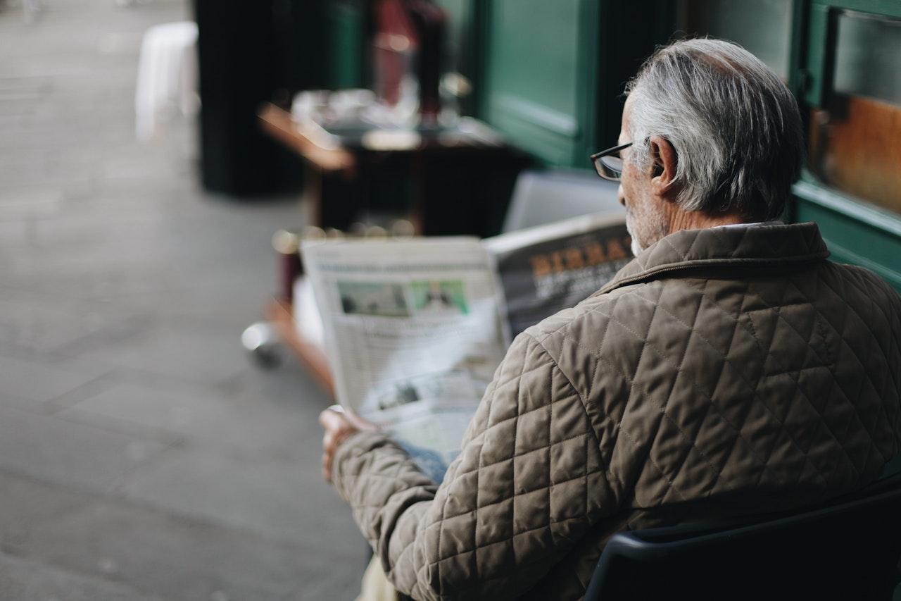 man-sitting-reading-newspaper-1684916