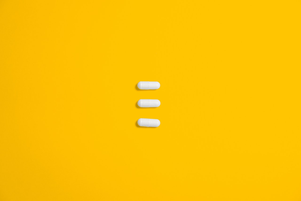 white-three-oval-capsule-on-yellow-canvas-3683108