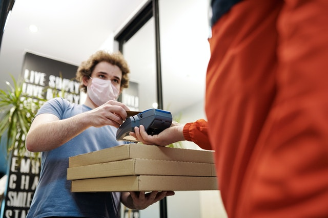 man-wearing-a-face-mask-paying-for-pizza-delivery-4393529