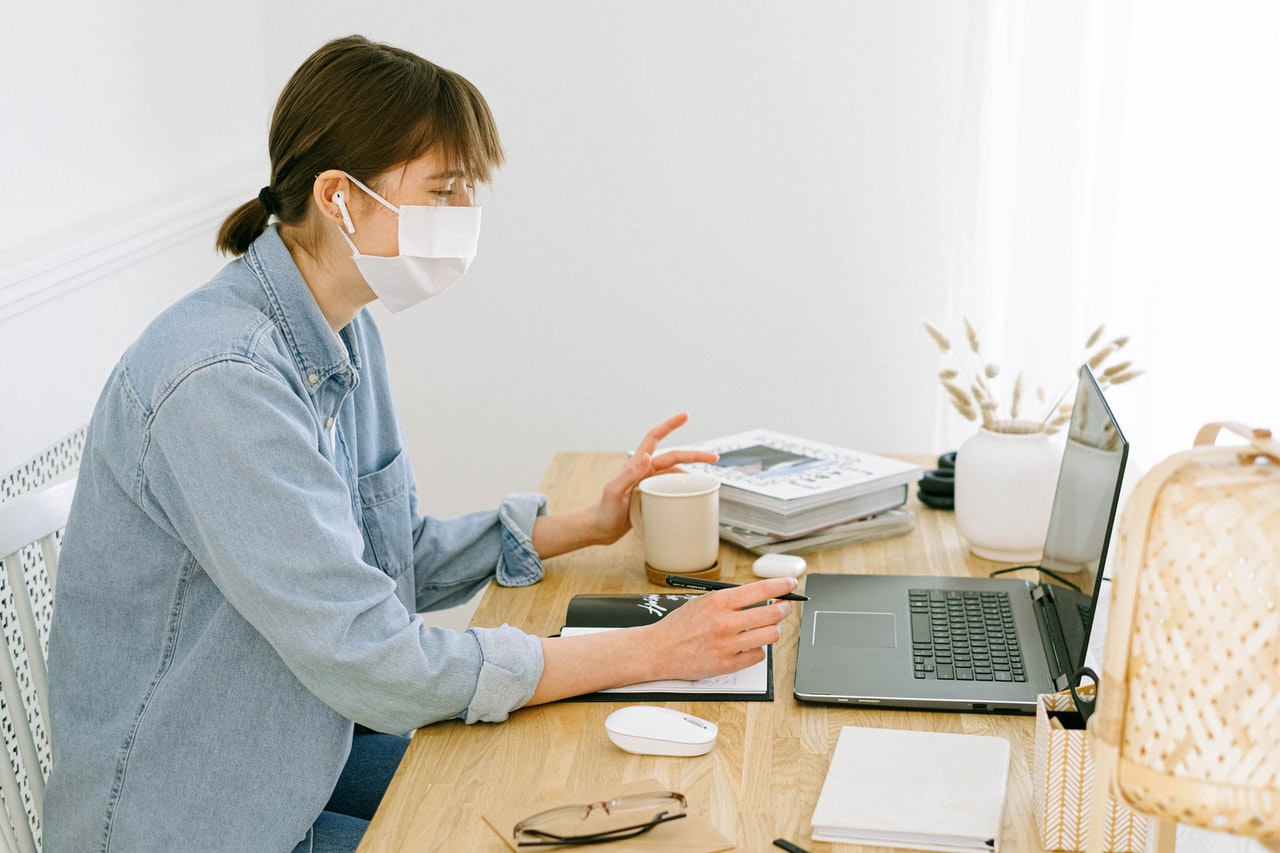 woman-with-face-mask-looking-at-a-laptop-4240606